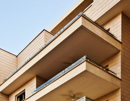 בניין עם מעקות זכוכית במרפסות